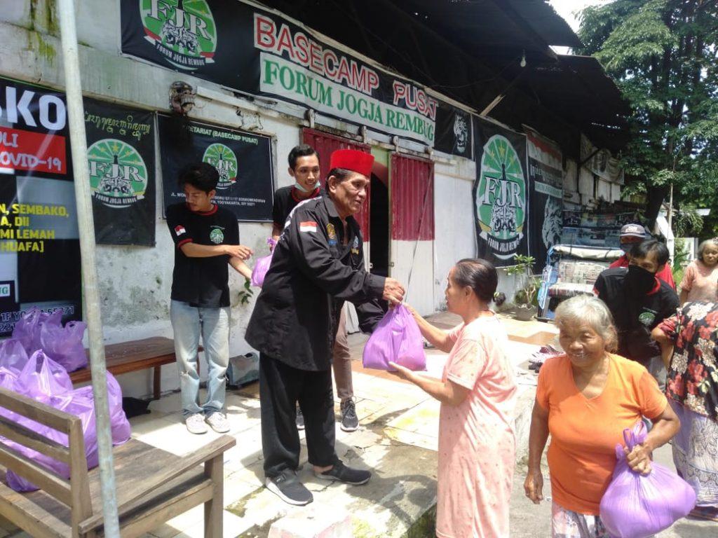 Ketua Forum Jogja Rembug (FJR) Cak Harno membagi-bagikan sembako gratis